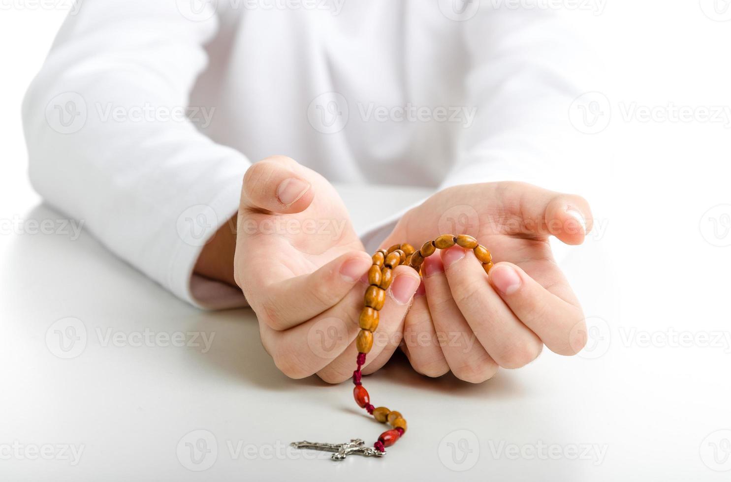mani del bambino offrono rosari di legno foto