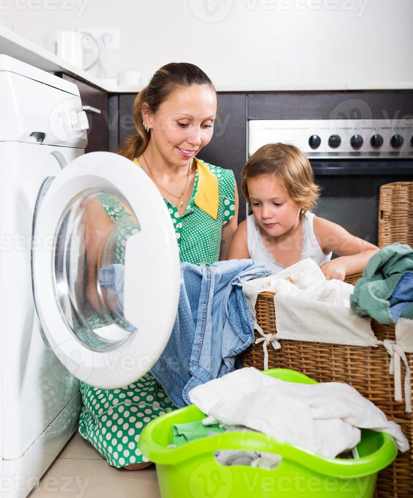 donna con bambino vicino alla lavatrice foto