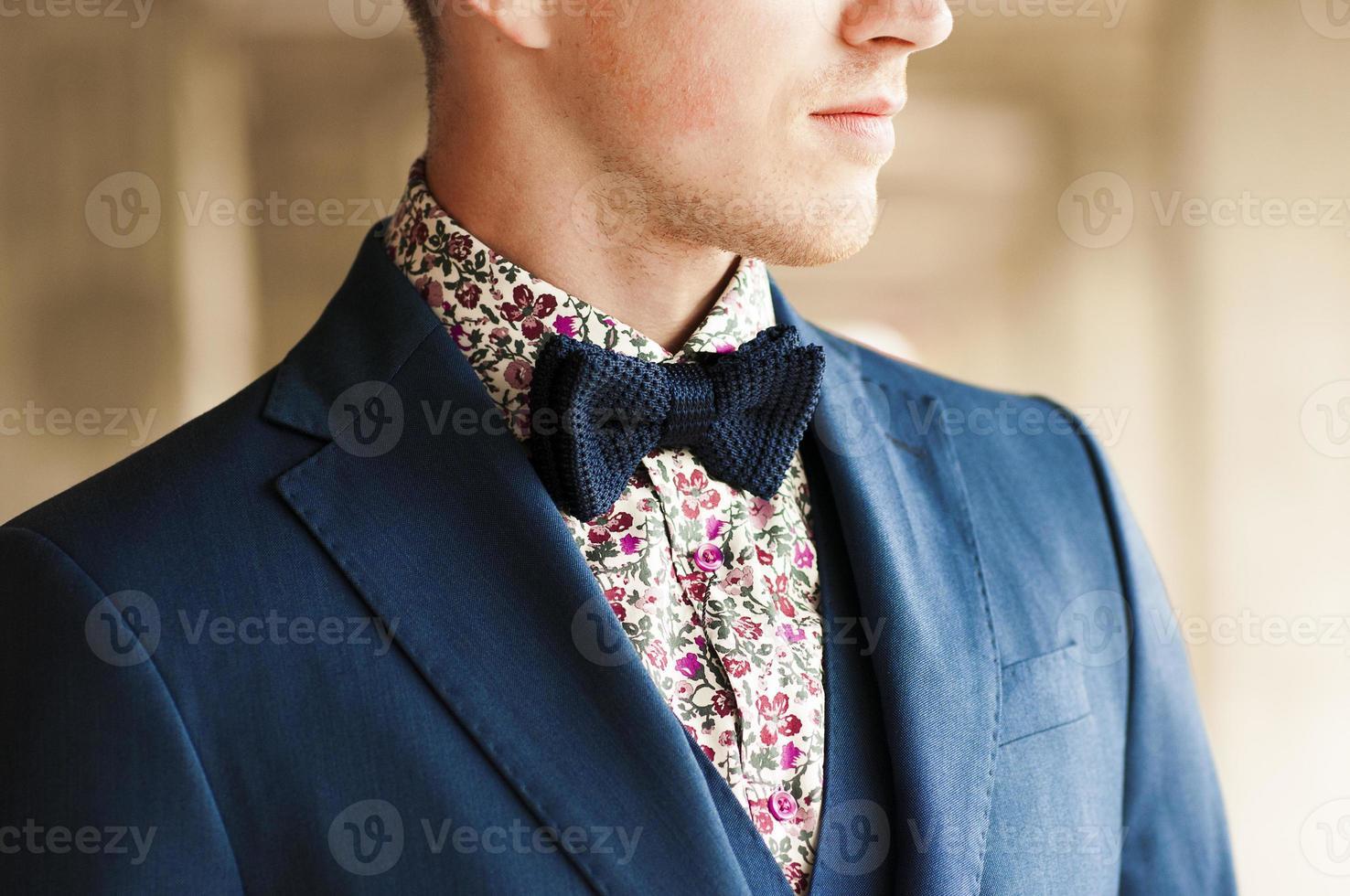 Papillon blu scuro con camicia a fiori sul collo da uomo. foto