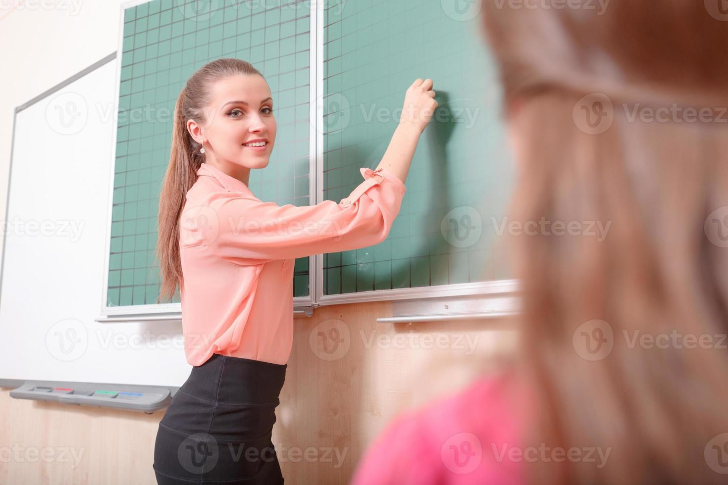 giovane insegnante femminile scrivendo sulla lavagna foto