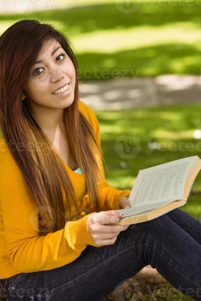 libro di lettura rilassato della studentessa in parco foto