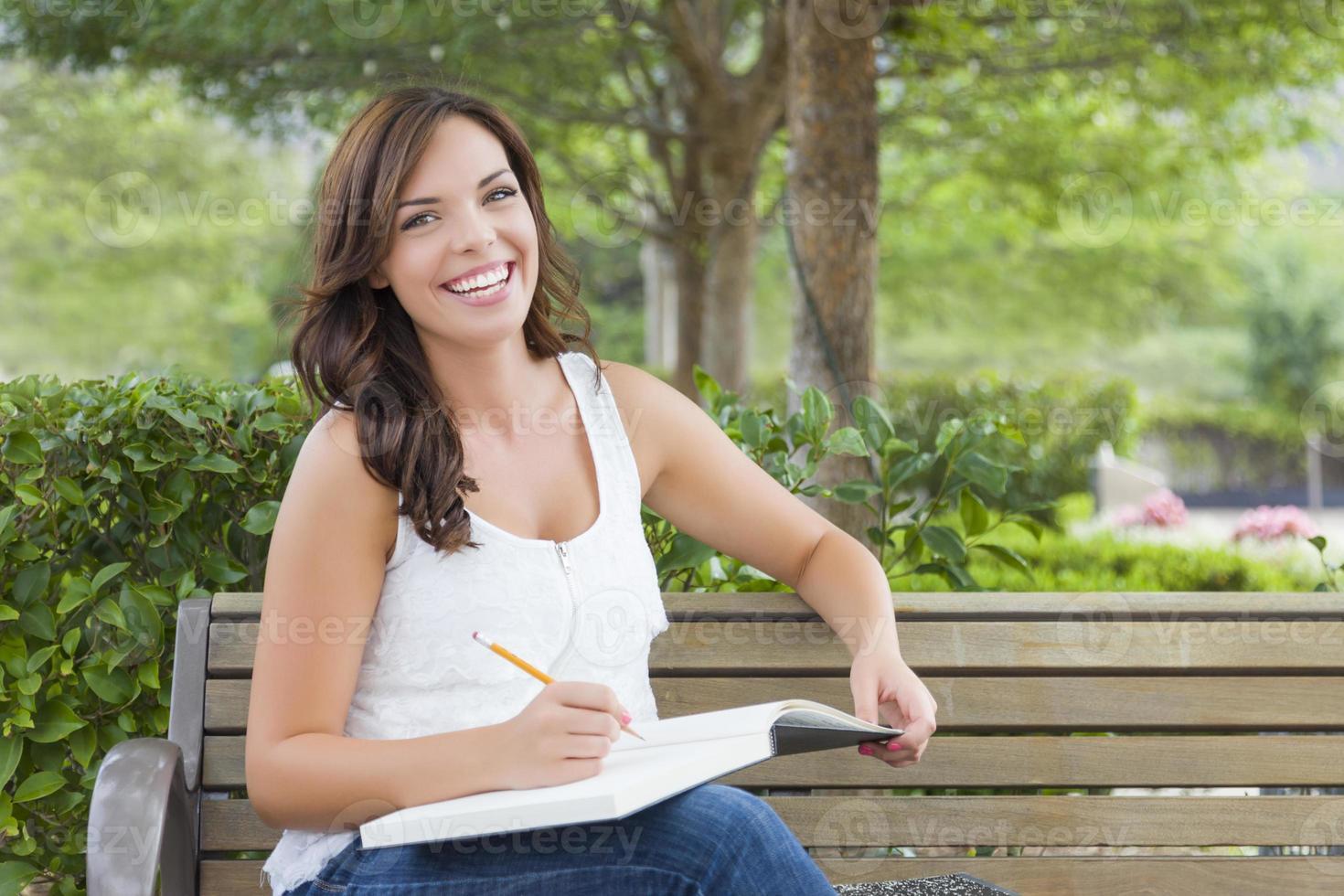 giovane studentessa adulta sul banco all'aperto foto