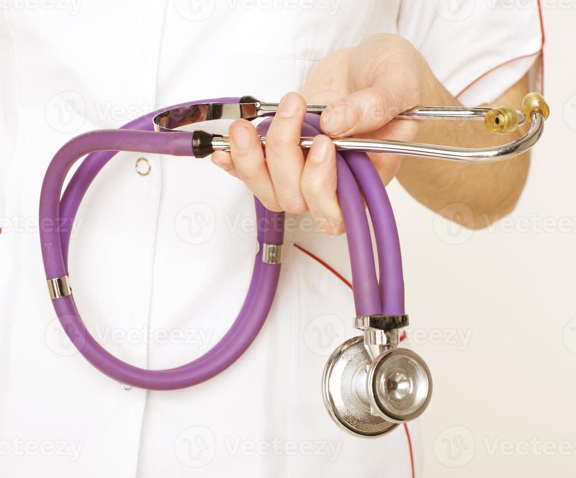 primo piano del medico femminile che per mezzo dello stetoscopio foto