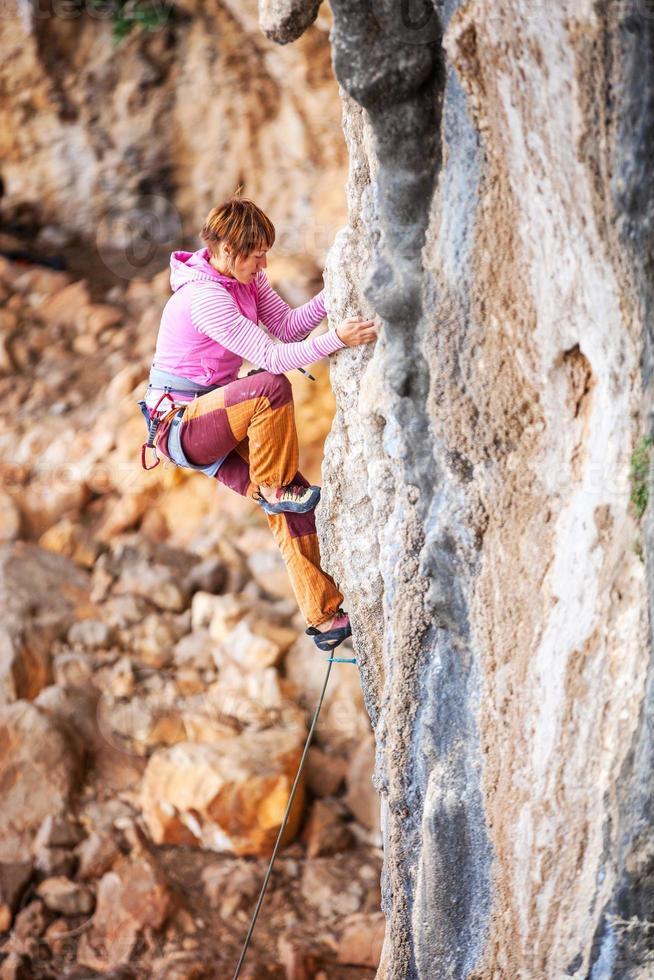 giovane scalatore femminile sulla scogliera foto