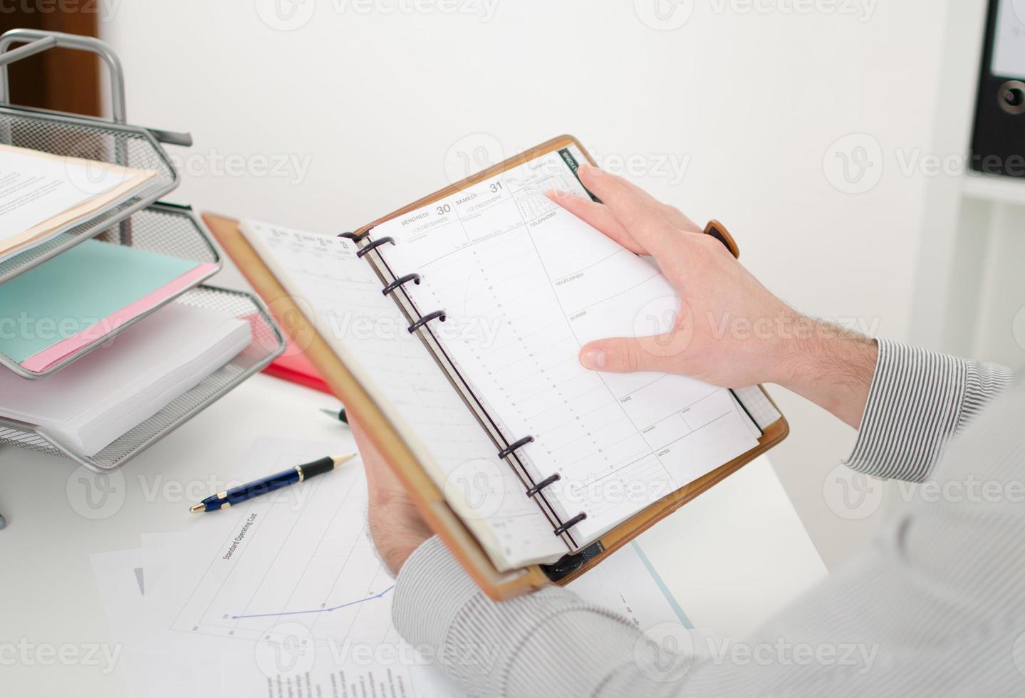 uomo d'affari consultando la sua agenda foto