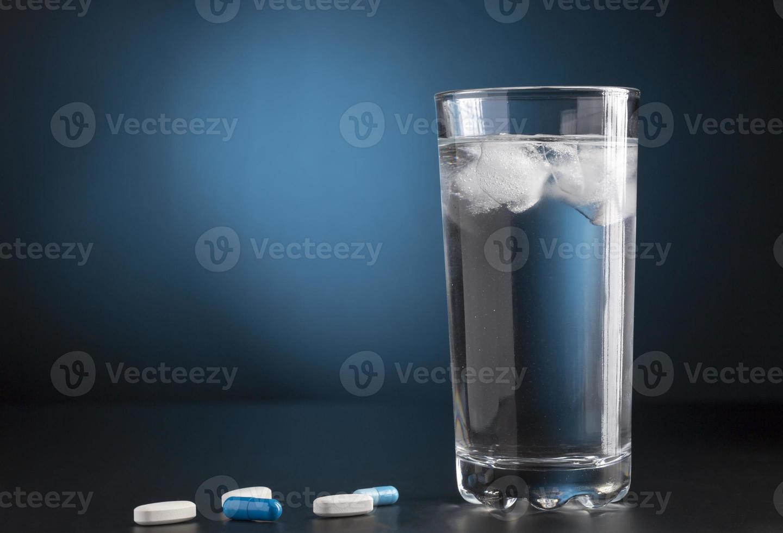 pillole di medicina e bicchiere di acqua fredda per bevande foto