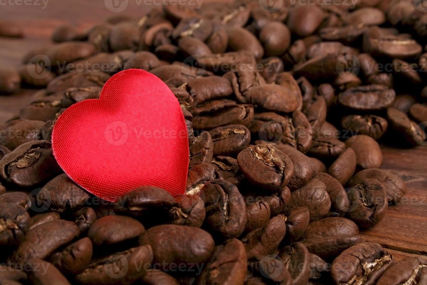 chicchi di caffè e cuore rosso su fondo di legno foto