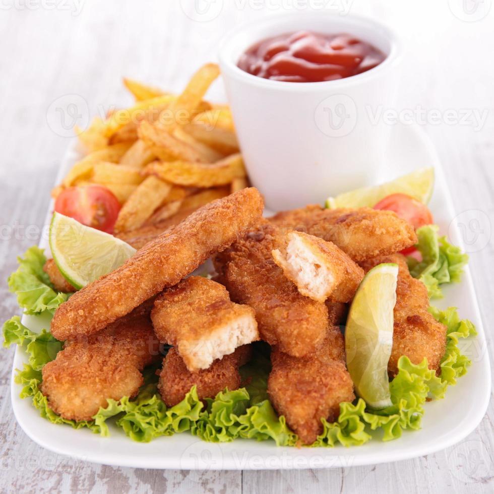 piatto di bocconcini di pollo e patatine fritte foto