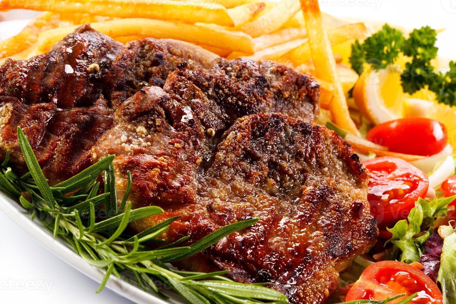 bistecche alla griglia, patatine fritte e verdure foto