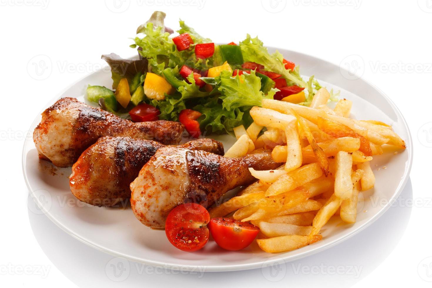 cosce di pollo arrosto, patatine fritte e verdure foto