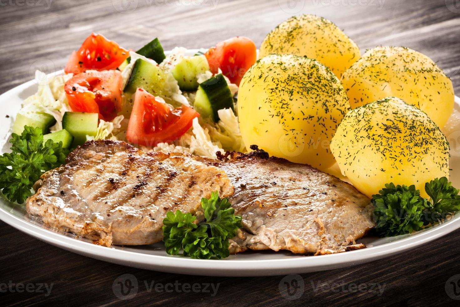 bistecca alla griglia, patate lesse e verdure su fondo di legno foto