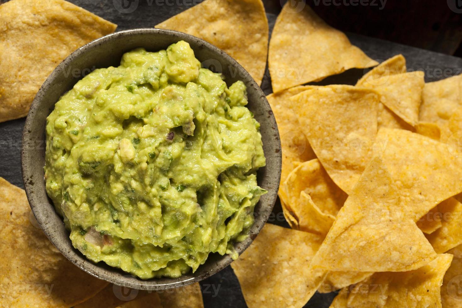 guacamole verde fatto in casa con tortilla chips foto