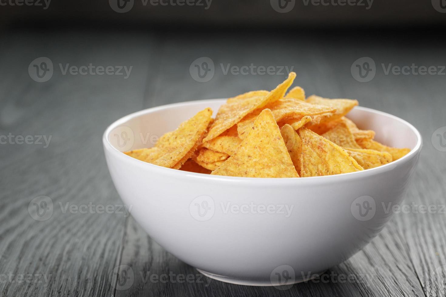 tortilla chips in una ciotola bianca con salsa di pomodoro sul tavolo foto