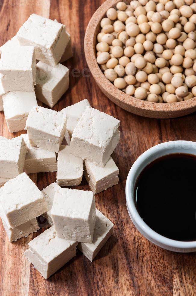 pezzo di tofu e fagioli di soia su un tagliere foto