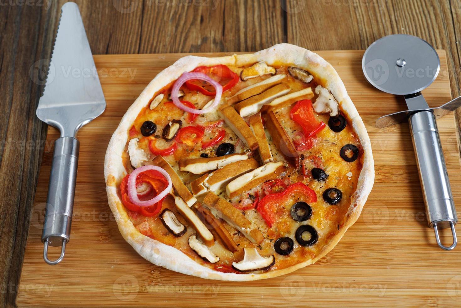 Pizza margarita vegetariana fatta in casa sul tavolo foto