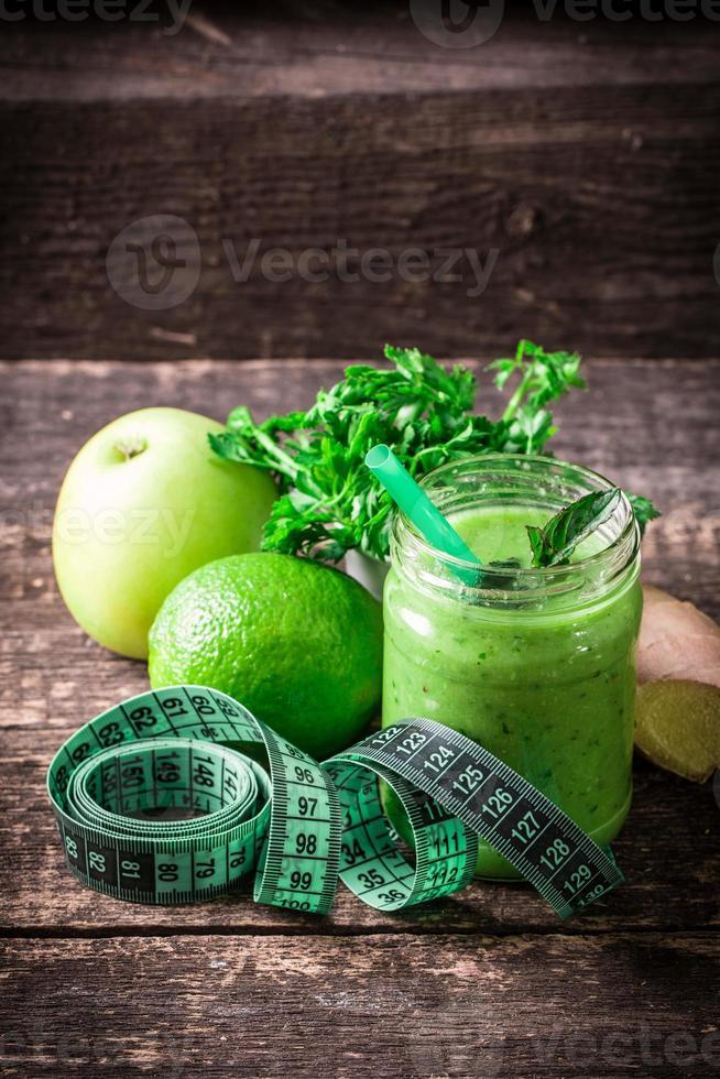 frullato di disintossicazione verde sul tavolo di legno foto