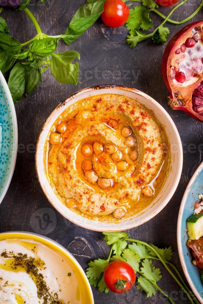 tavolo servito con piatti vegetariani del Medio Oriente. hummus, tahi foto