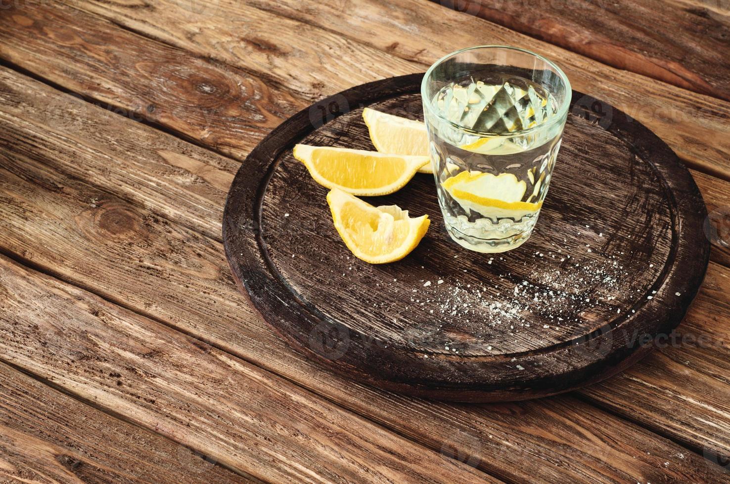 bicchiere di tequila con fettine di limone su uno sfondo di legno foto