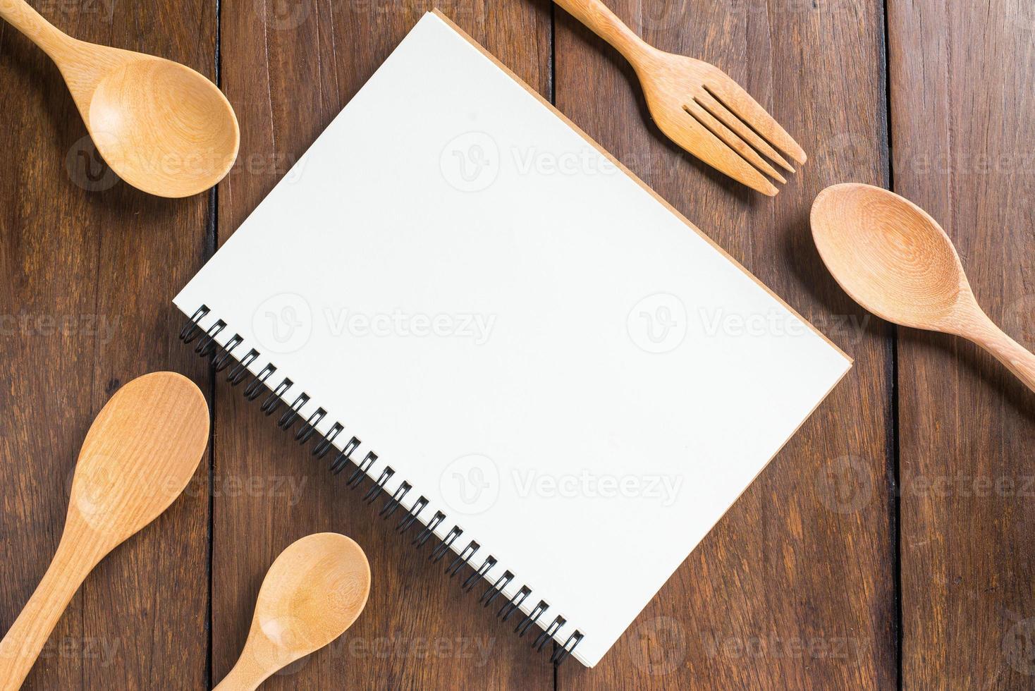 taccuino di ricetta, cucchiaio, forchetta su fondo di legno foto