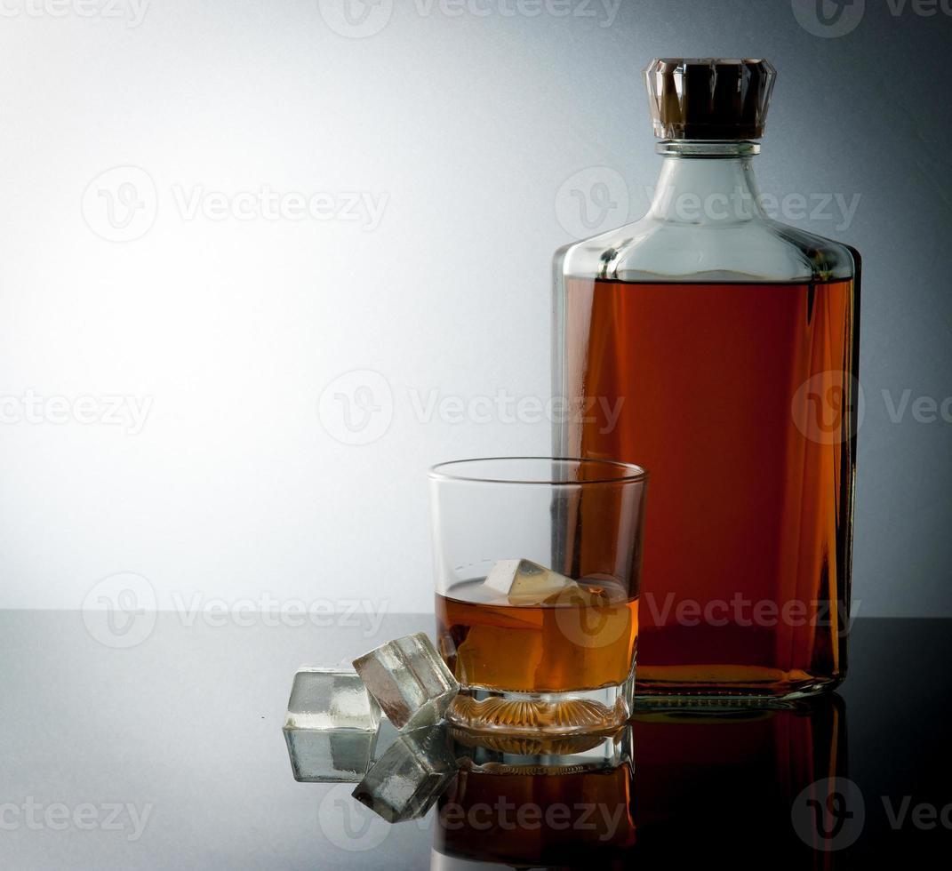 bicchiere e bottiglia con cubetti di ghiaccio foto