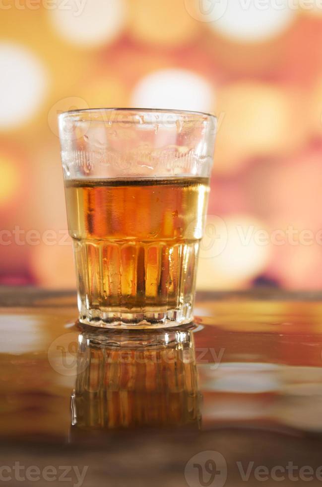 bicchiere di whisky al rum su sfondo di luci sfocati foto