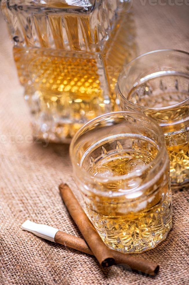 Close up di sigari e bicchieri di whisky foto