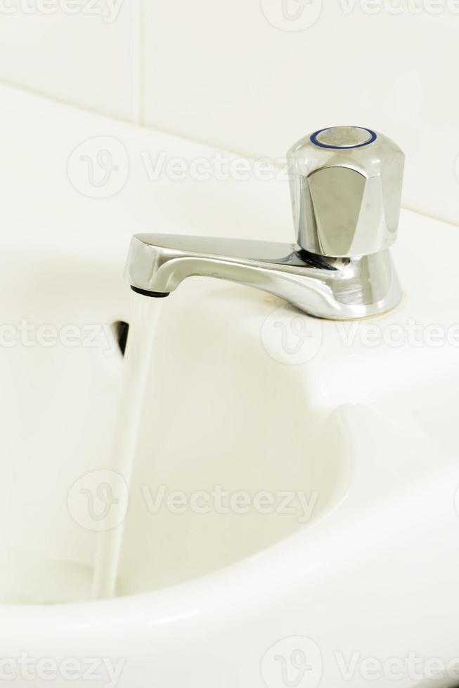 rubinetto aperto con acqua corrente foto