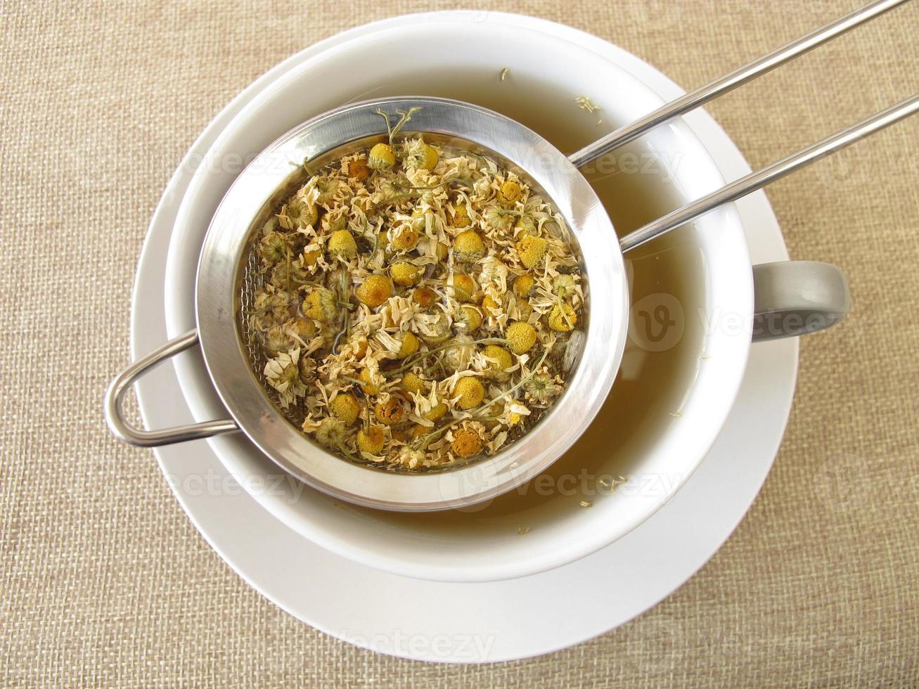 tè di fiori di camomilla in colino da tè foto