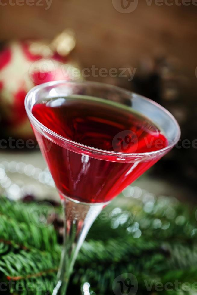 cocktail di Natale rosso in un bicchiere da martini con rami di abete foto