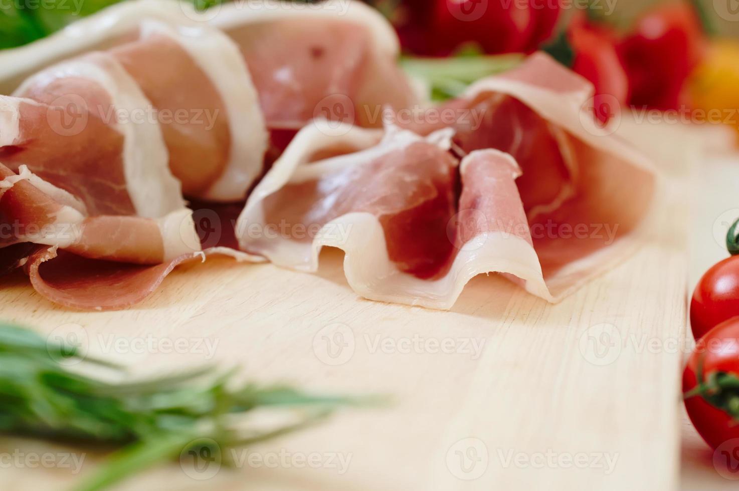 prosciutto crudo e pomodori freschi crudi ed erbe aromatiche, basilico e rosmarino foto