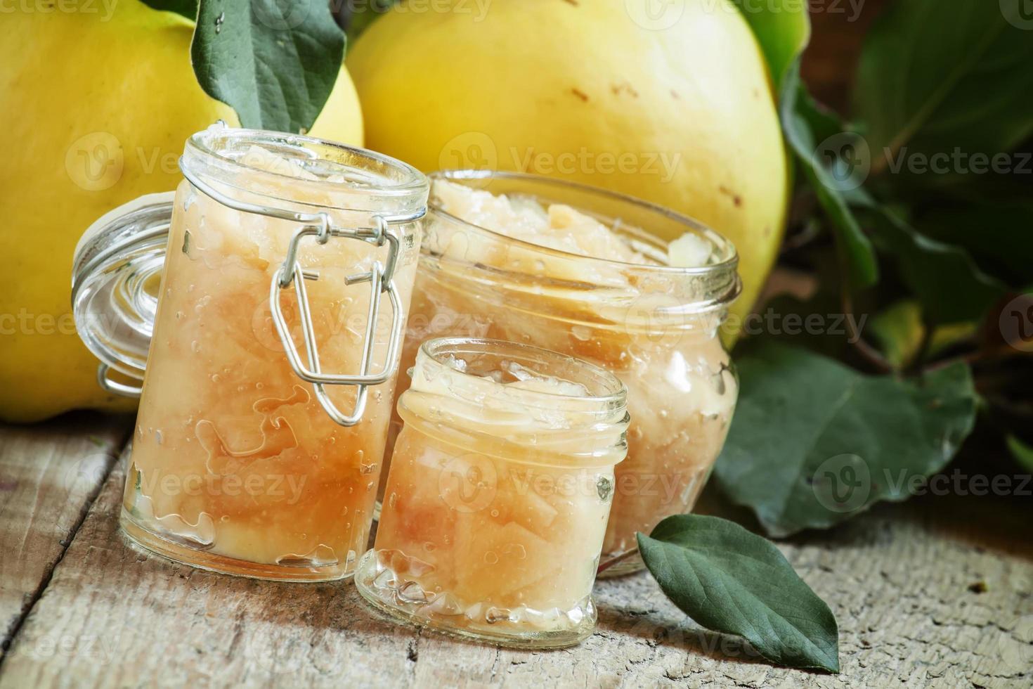 marmellata di mele cotogne rosa in vasetti di vetro e mela cotogna fresca foto