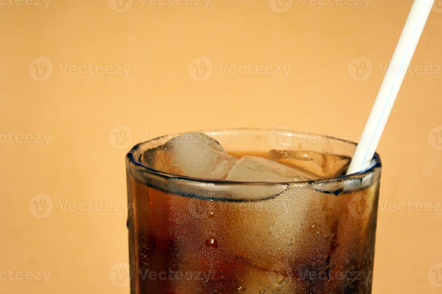 bicchiere di cola e ghiaccio con una cannuccia foto