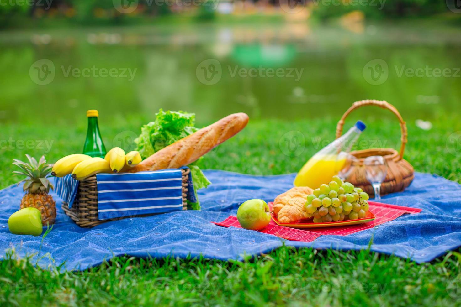 cestino da picnic con frutta, pane e bottiglia di vino bianco foto