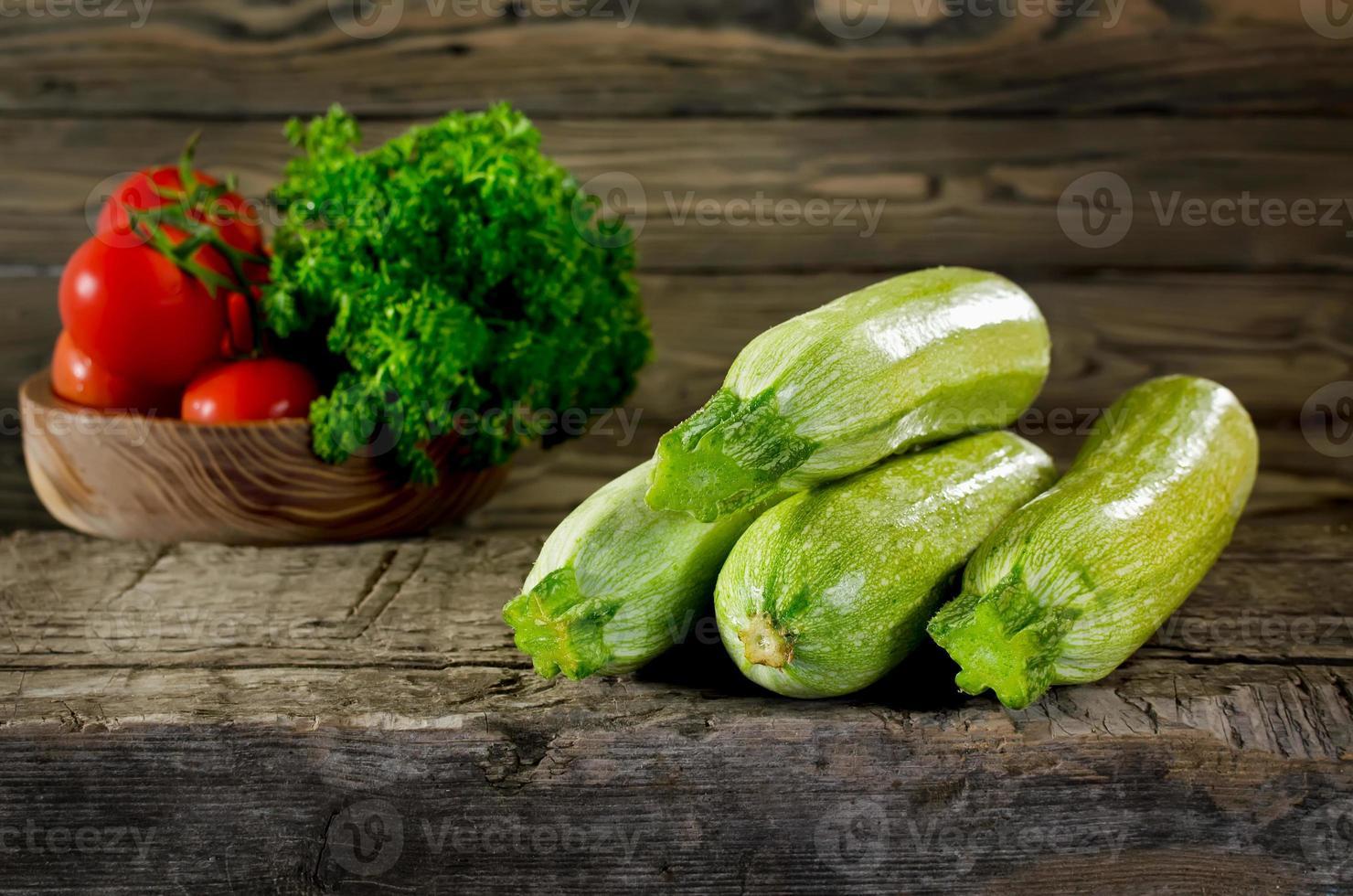 zucchine, pomodori e prezzemolo su fondo in legno. zucchine cl foto
