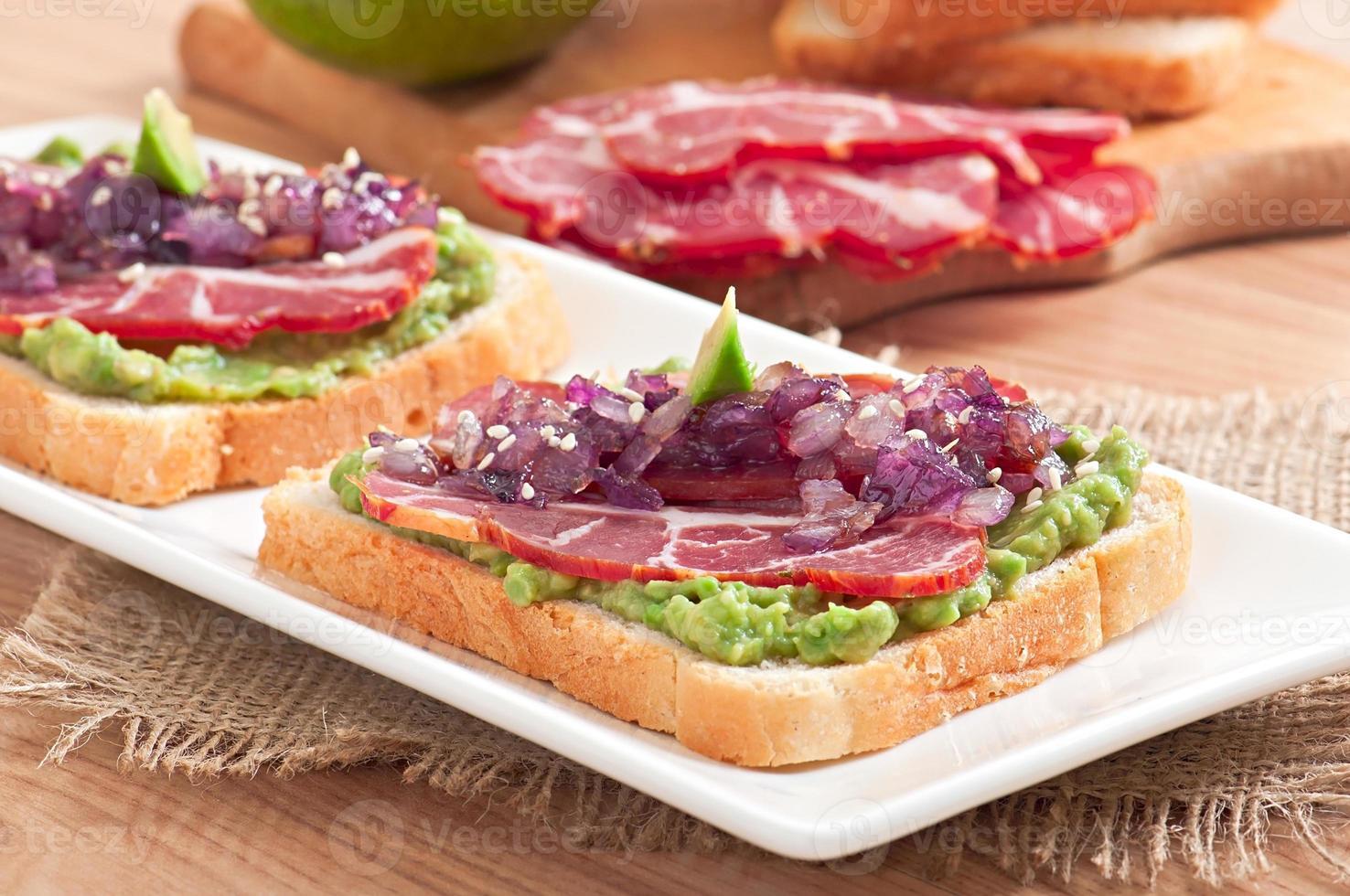 sandwich con prosciutto, salsa di avocado e cipolle caramellate foto