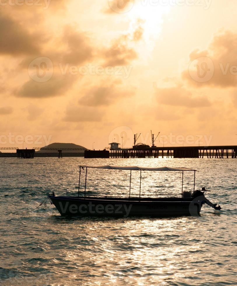 peschereccio sull'acqua e nuvole drammatiche all'alba foto