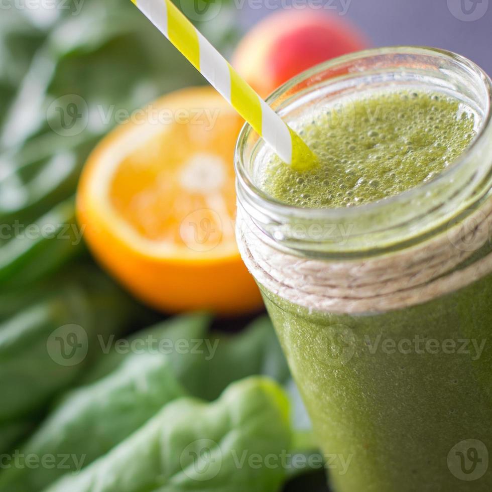 frullato verde mescolato con il fuoco selettivo degli ingredienti foto
