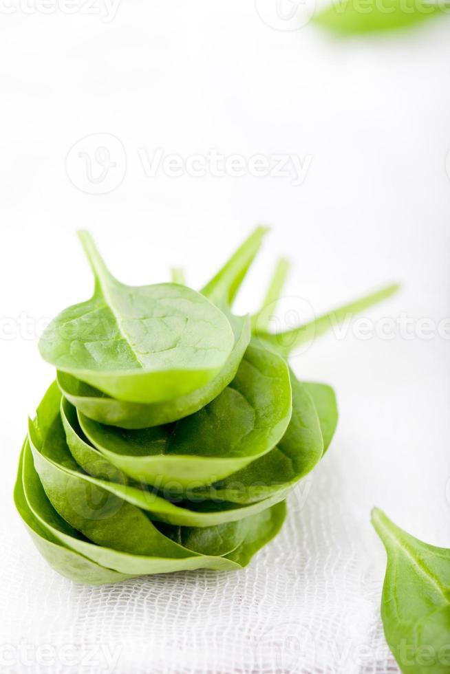 foglie di spinaci su un fondo di legno bianco. foto
