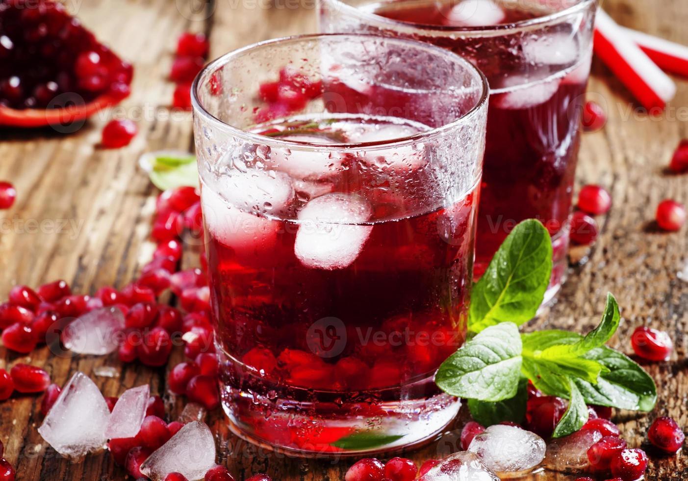 cocktail di succo rosso fresco con semi di melograno, menta e ghiaccio foto