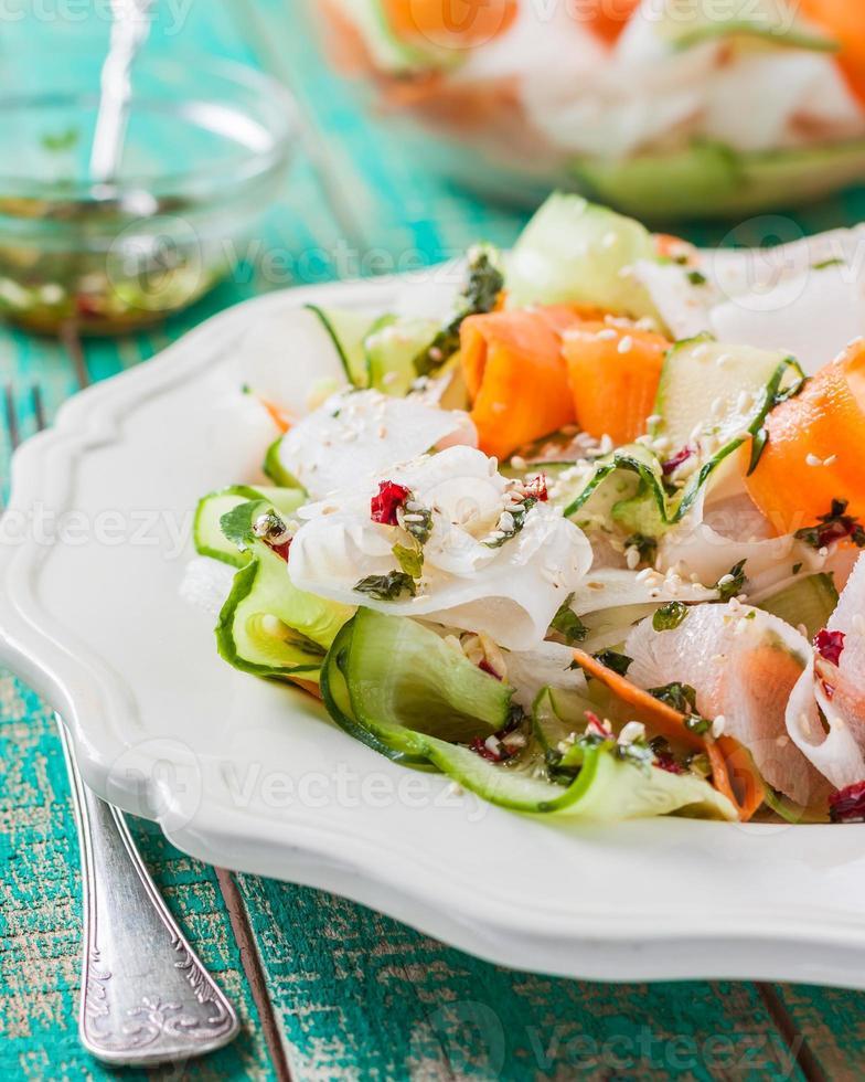 insalata di carota, cetriolo e ravanello daikon sul tavolo di legno foto