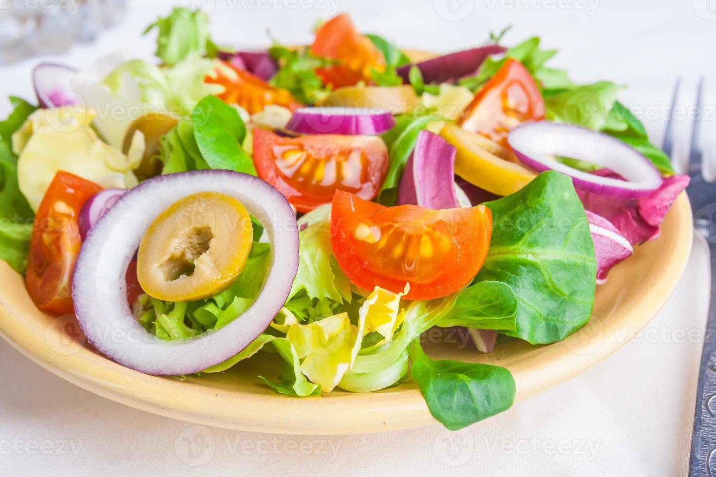 insalata vegetariana con lattuga, pomodori, olive e cipolle foto