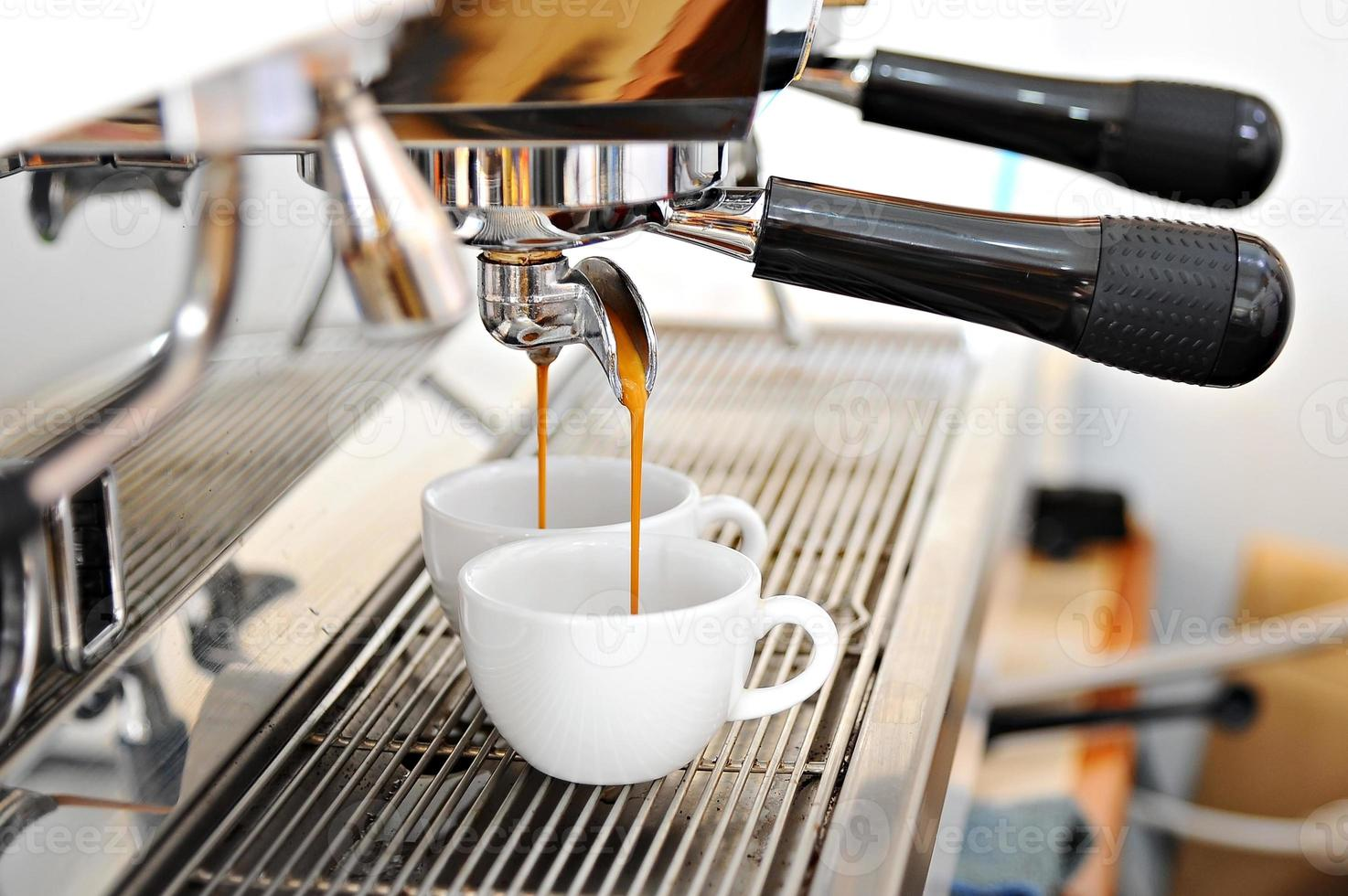 la macchina da caffè produce due tazze di caffè caldo foto