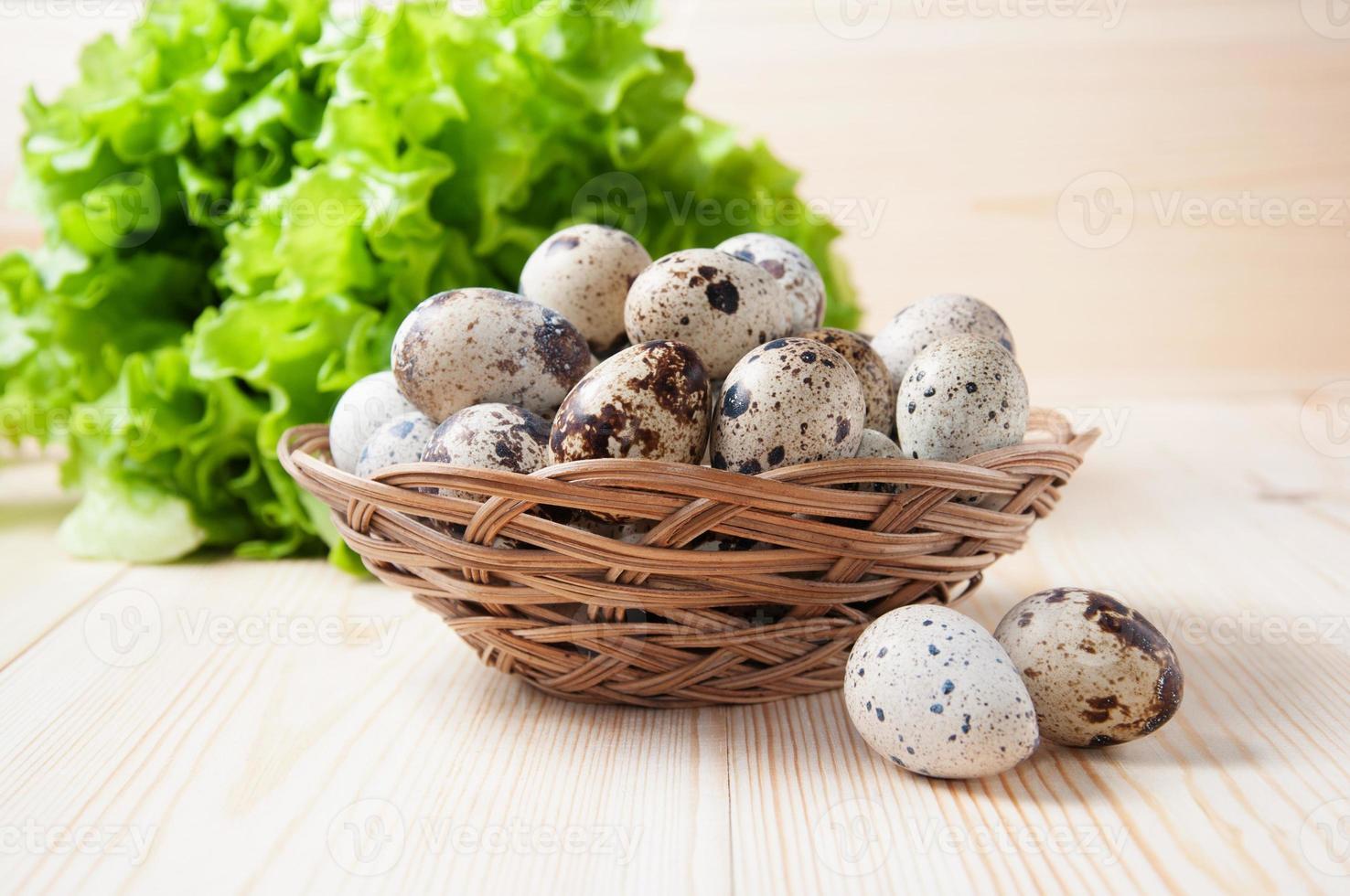 uova di quaglia in una ciotola di vimini e insalata verde foto