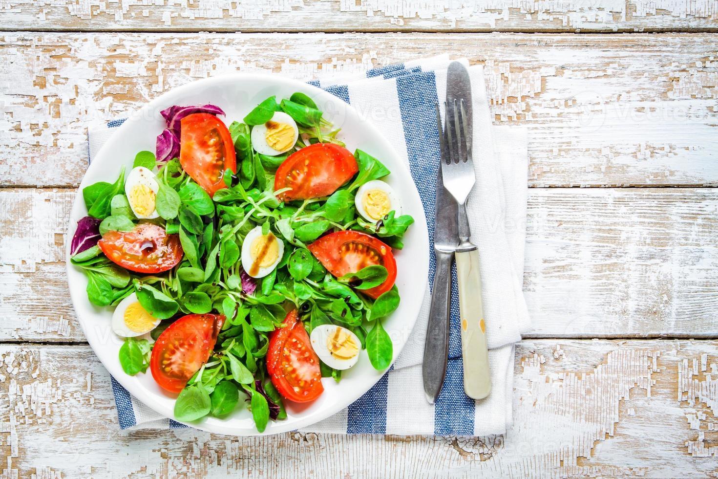 insalata verde fresca con lattuga di agnello, pomodori e uova di quaglia foto