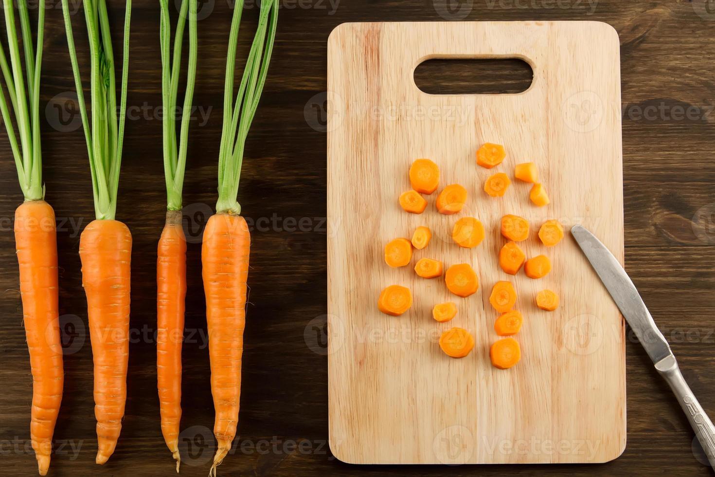 mazzo di carote fresche con le foglie verdi su di legno foto
