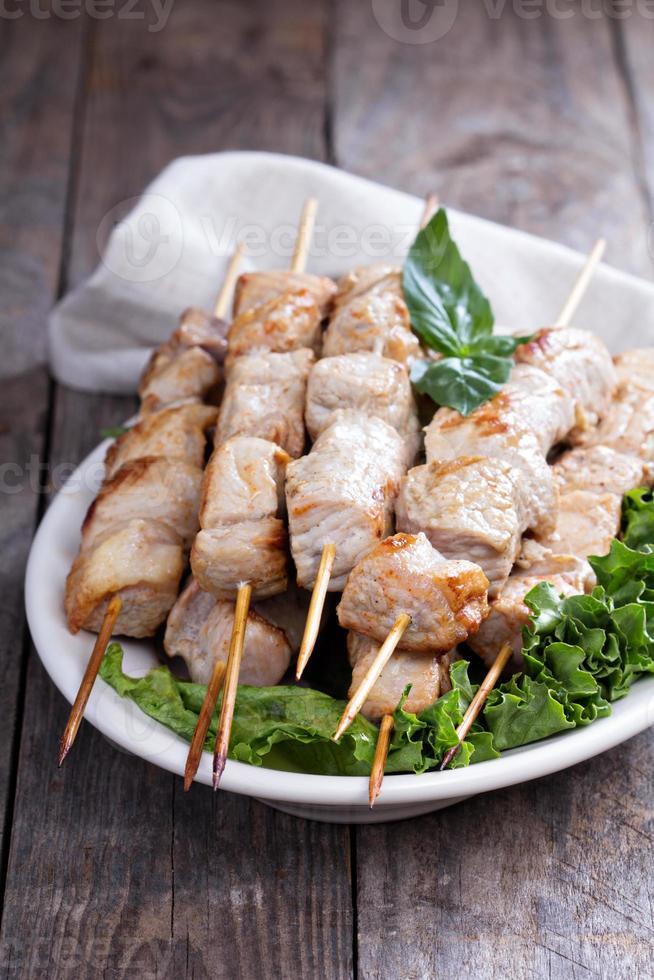 spiedini di maiale con foglie di insalata fresca foto