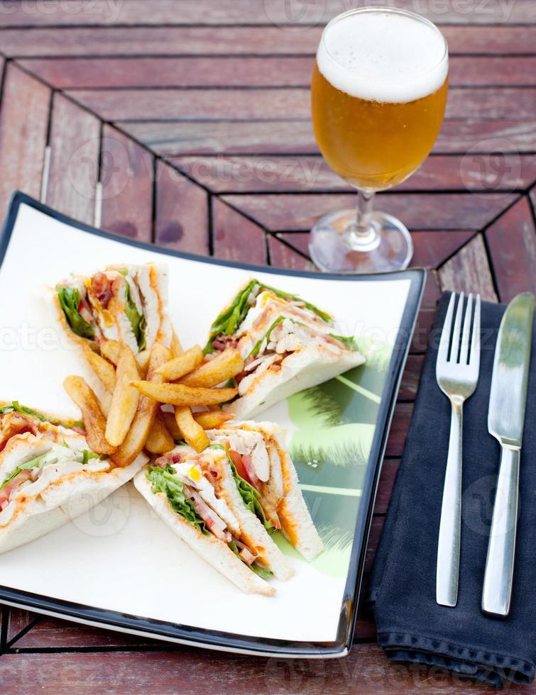 club sandwich con patatine fritte e una birra foto