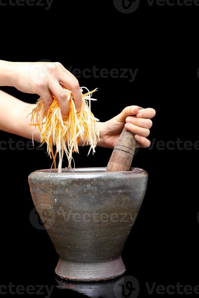 mano che tiene papaia cruda con mortaio di argilla tradizionale tailandese foto