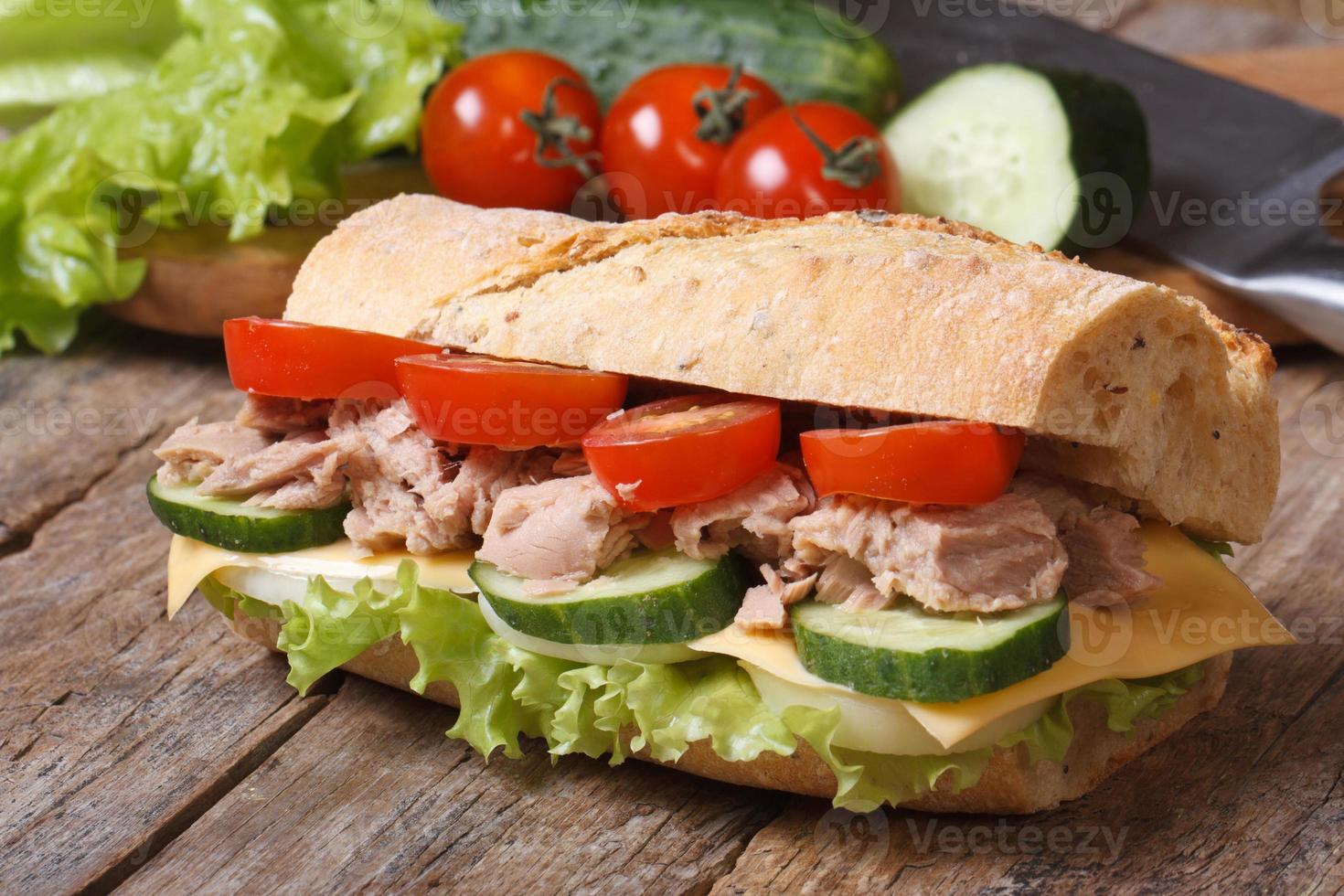 panino al tonno con verdure su sfondo di ingredienti. foto