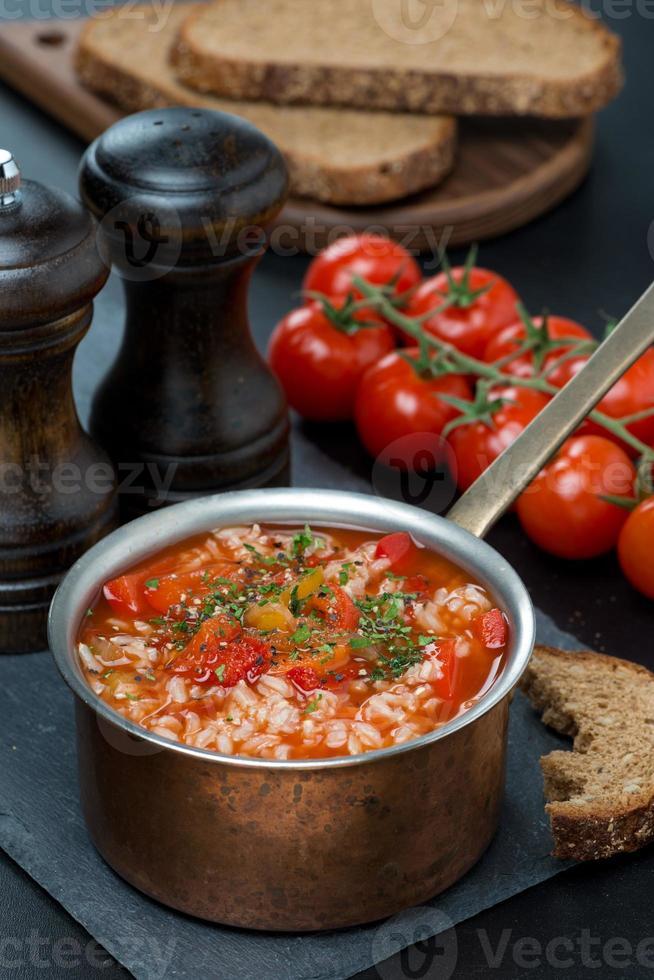 zuppa di pomodoro piccante con riso e verdure in una casseruola foto